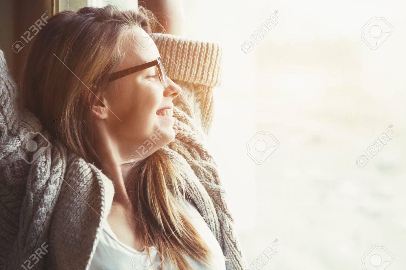 Woman near window raising hands facing the sunrise at morning - 57077244