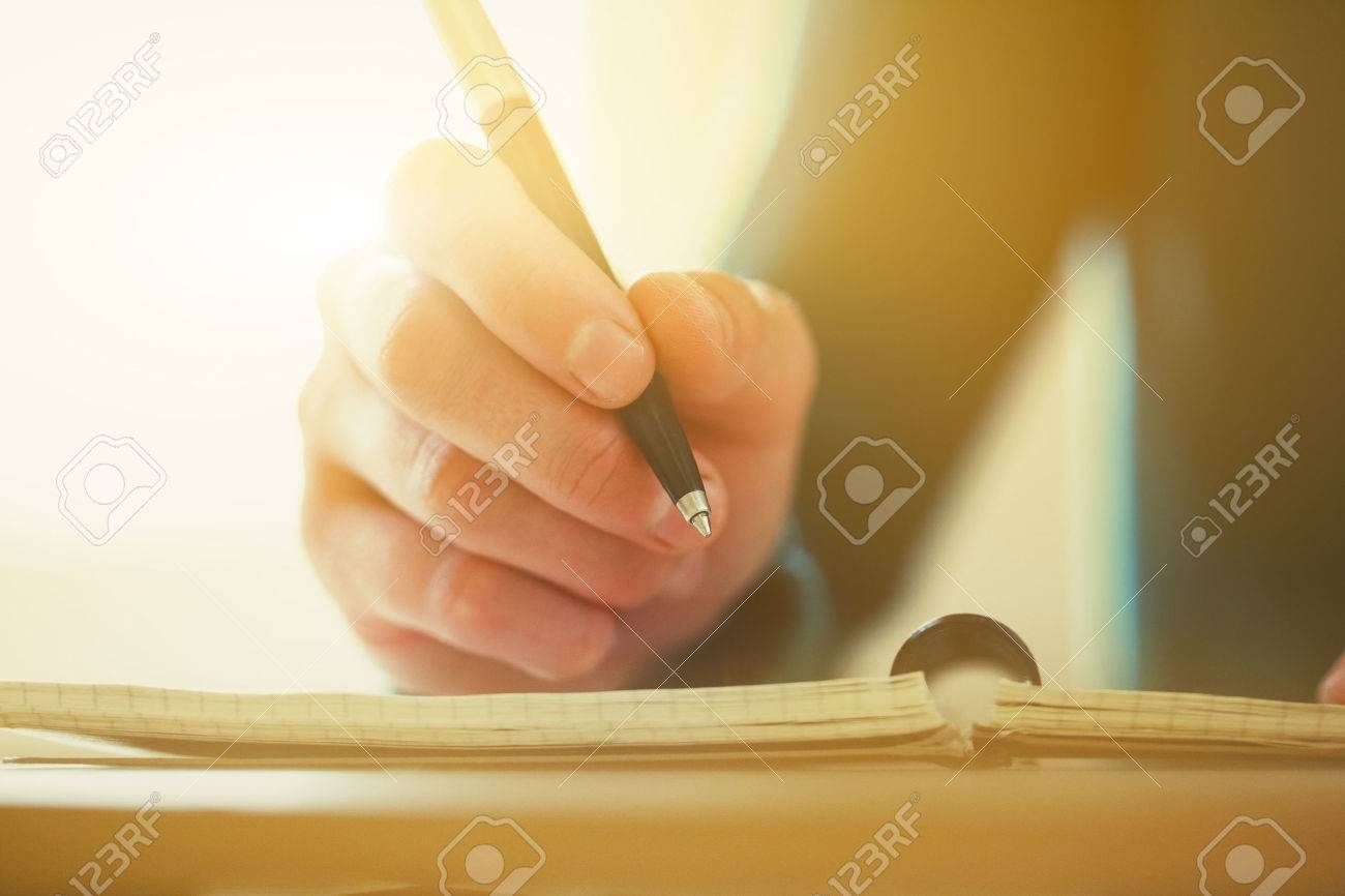 female hands with pen writing on notebook - 57077371