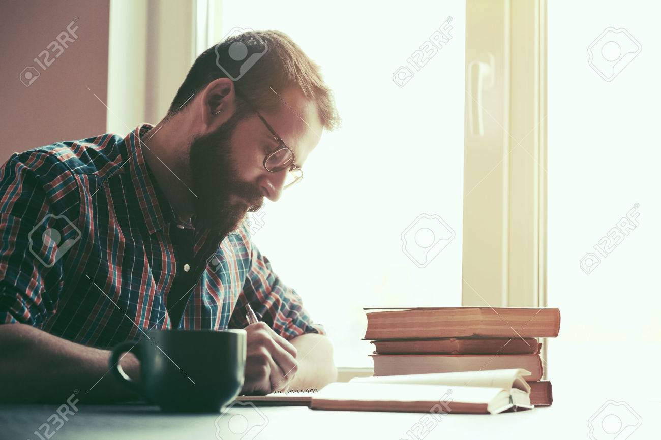 Bearded man writing with pen and reading books at table Stock Photo - 57106105