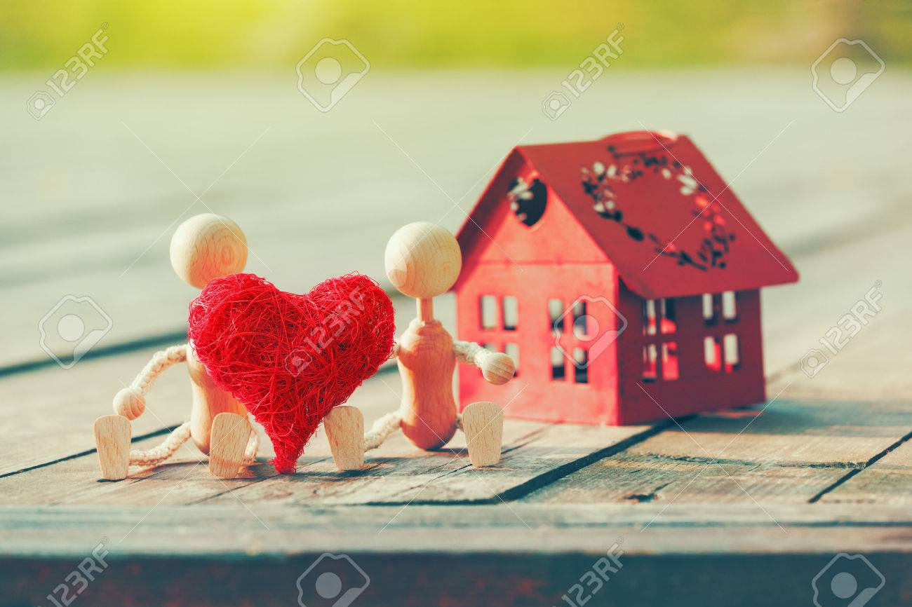Two wooden little men with heart near house Stock Photo - 61919899