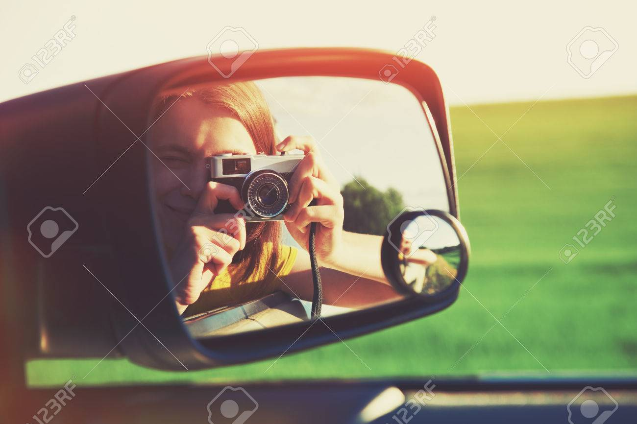 smiling girl taking photo with camera moving in car Stock Photo - 61920266