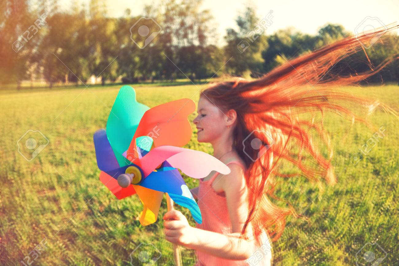 Happy redhead girl with pinwheel toy in motion blur. Freedom, summer, childhood concept Stock Photo - 61534242