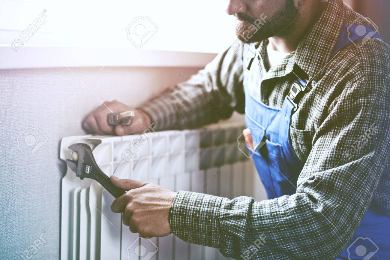 service man with wrench near radiator - 83918038