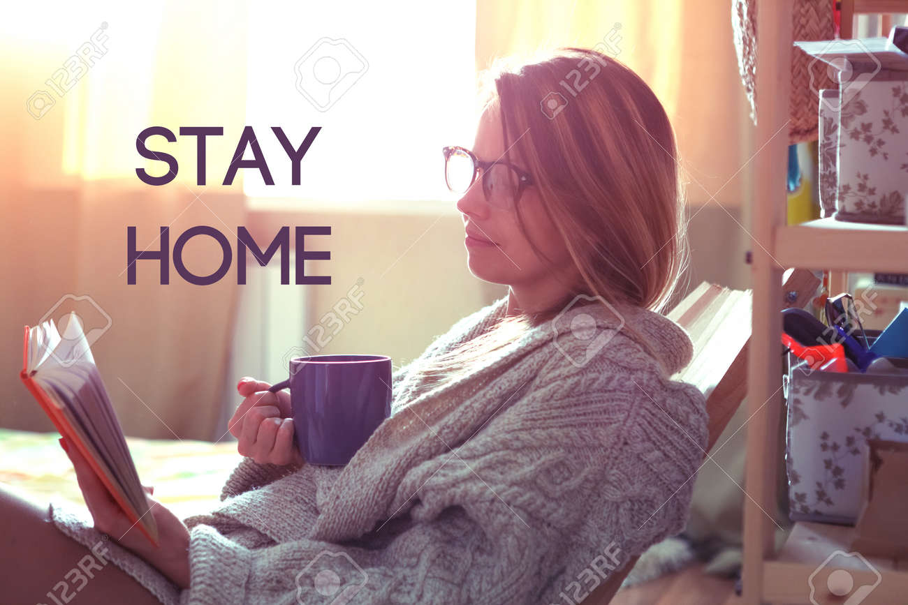 Pretty girl reading book with coffee and text Stay home. Home isolation and quarantine during coronavirus covid-19 pandemic. - 146254928