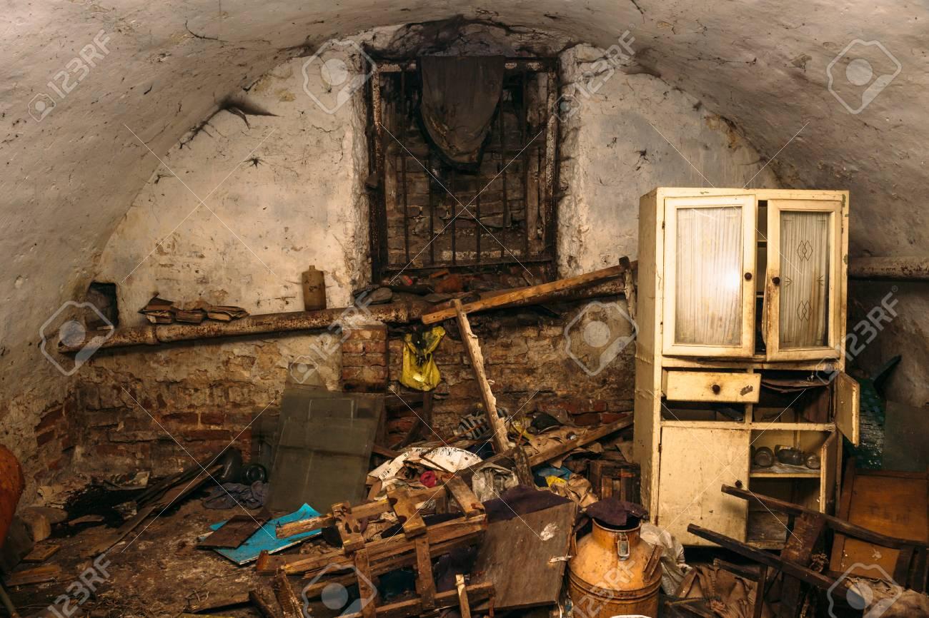 Viejo refugio sucio abandonado o sótano de personas sin hogar, muebles viejos y basura
