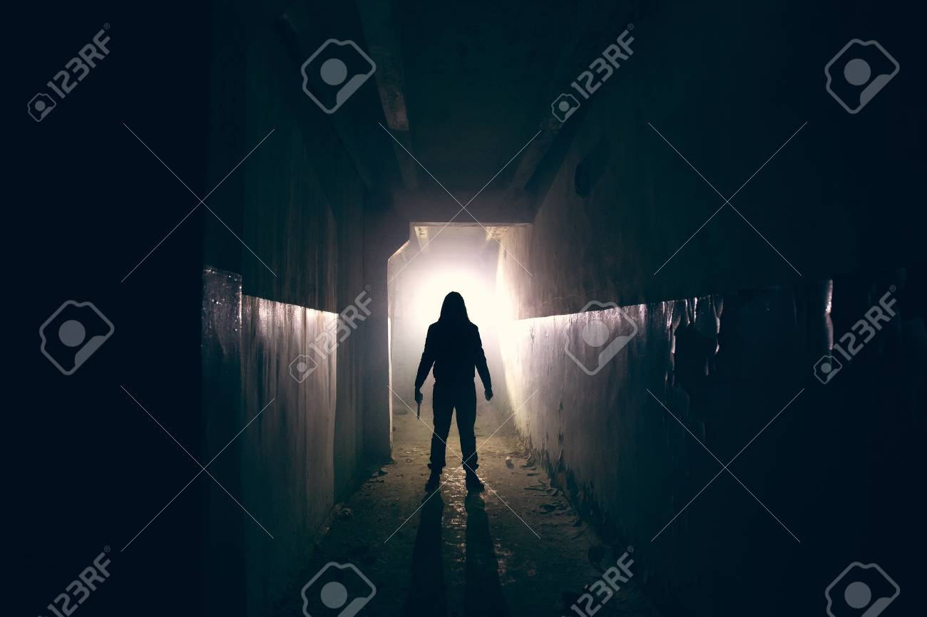 Silhouette of maniac with knife in hand in long dark creepy corridor, horror psycho maniac or serial killer concept, toned - 112854023