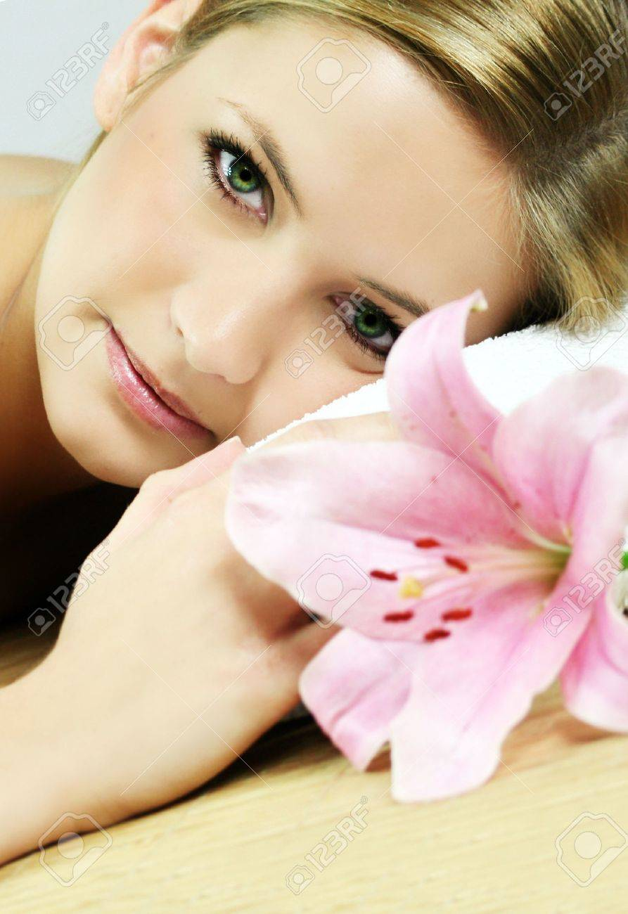 a young beautiful woman is relaxing in spa - wellness with a flower lily Stock Photo - 1455756