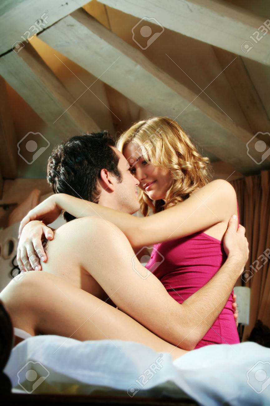 A Attractive Young And Happy Couple Embracing In Bed At Night Stock Photo