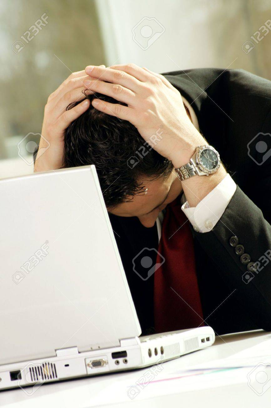 a business man is frustrated on a table with a laptop Stock Photo - 5064763