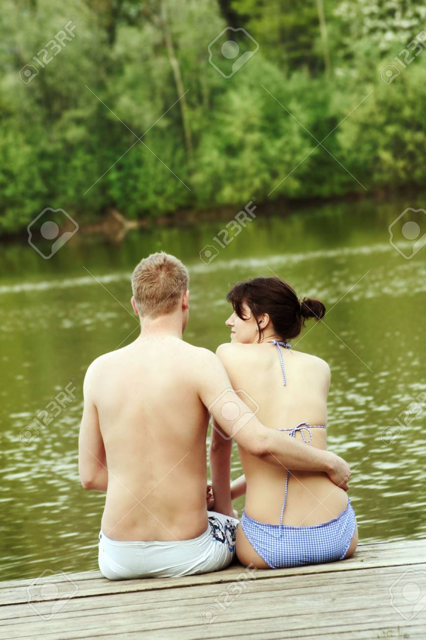 a happy young couple sitting on a lake Stock Photo - 5076017