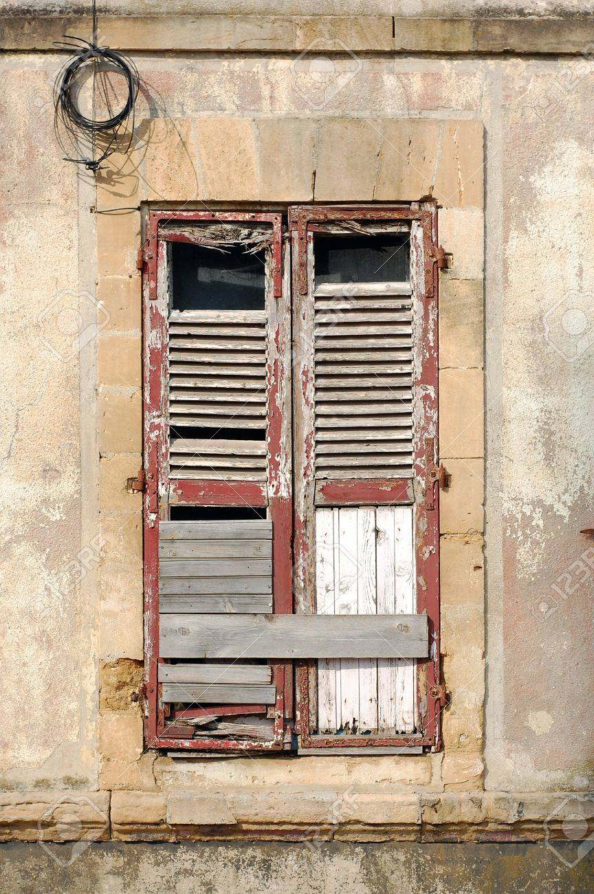 Boarded Up Wooden Window Shutters Of An Old Abandoned House In