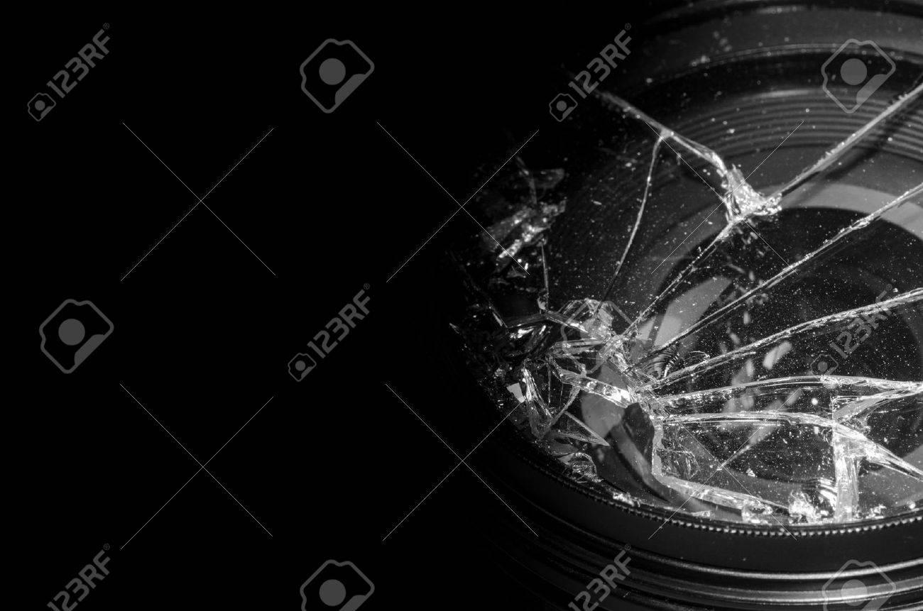 Broken DSLR camera lens on black background - 17408482