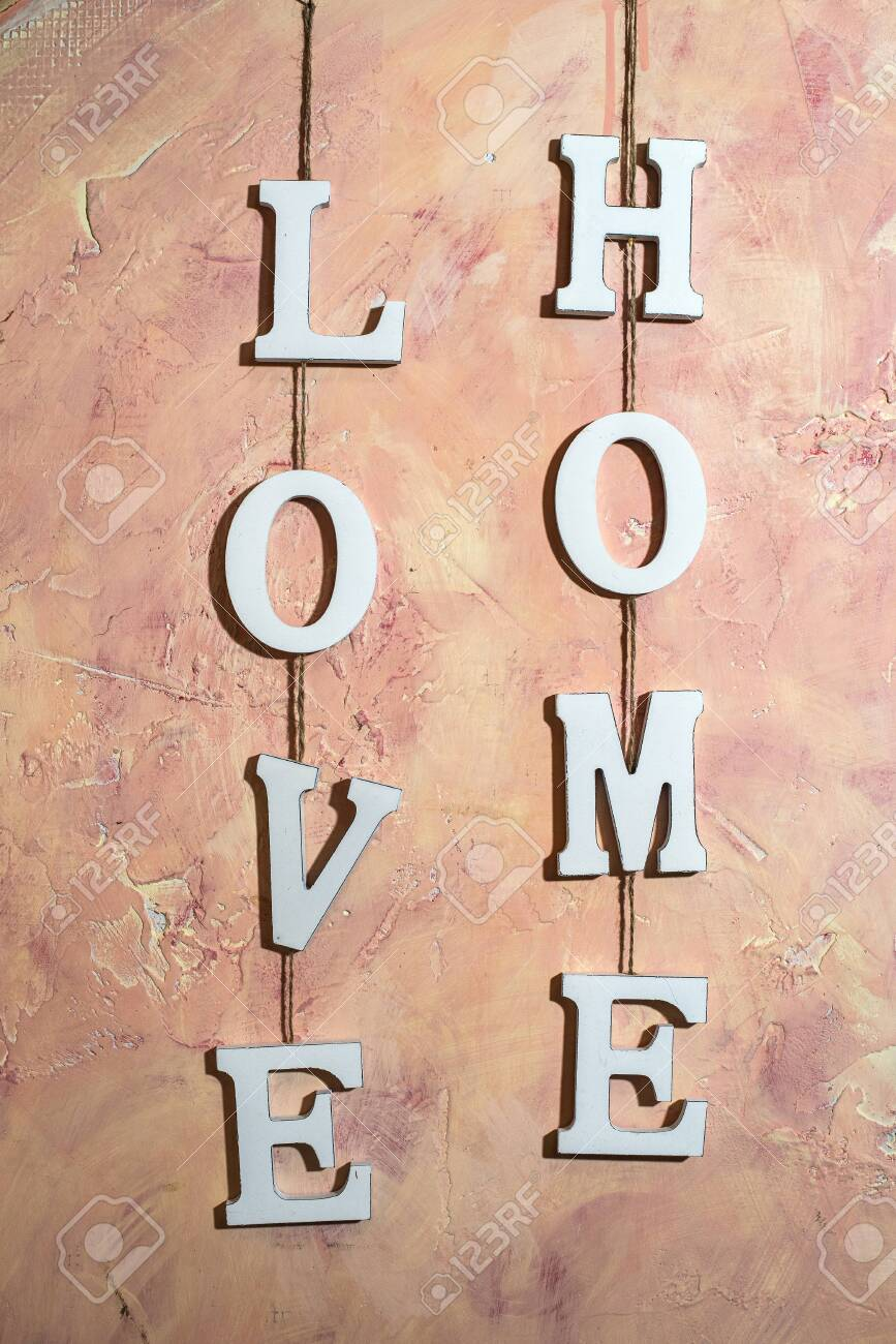 Love Home text on pink wall at home interior. White wooden charcters L O V E and H O M E hooked with rope on wall. Concept of love and home. - 115868616