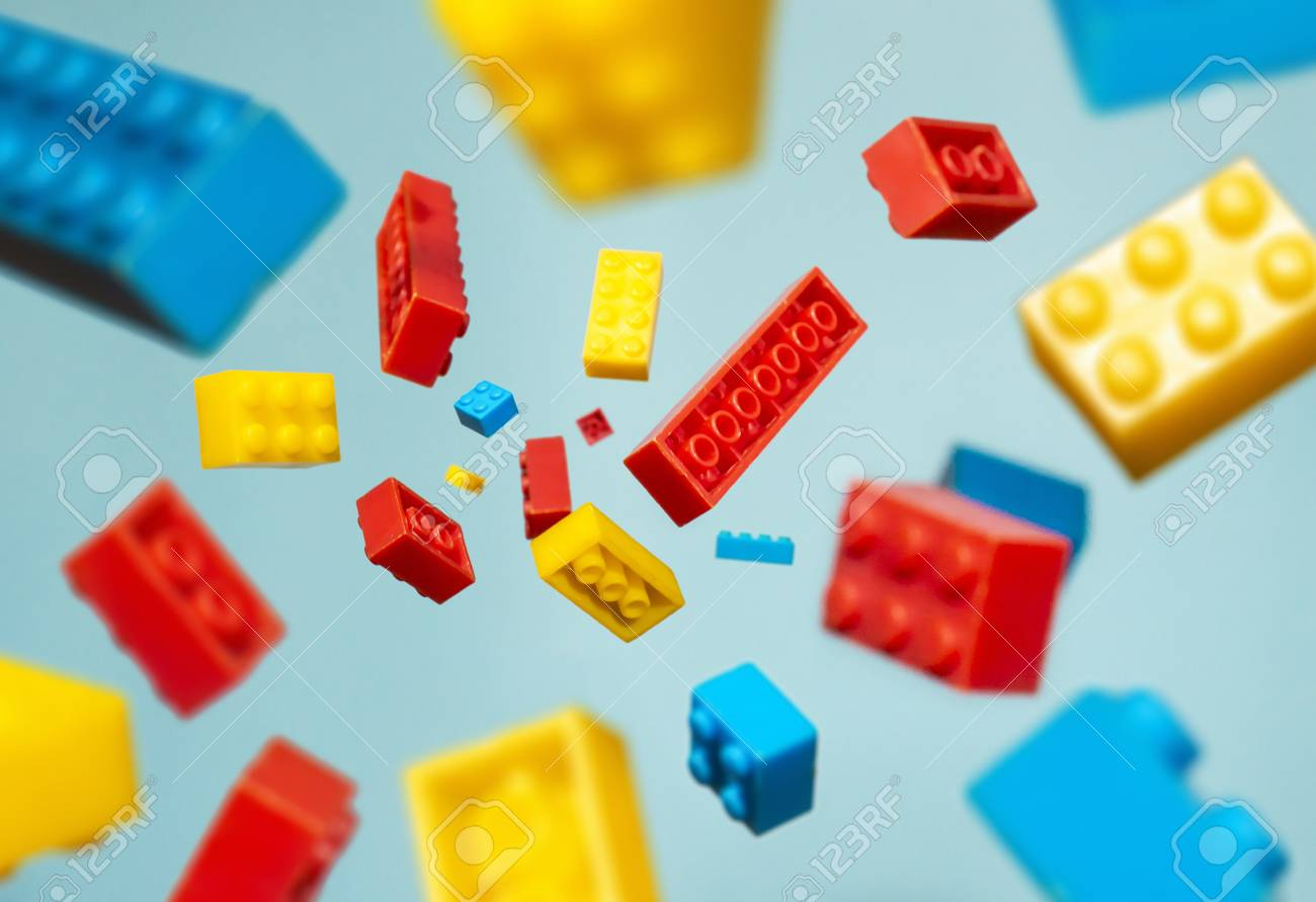 Floating Plastic geometric cubes in the air. Construction toys on geometric shapes falling down in motion. Blue pastel background. Children's toys. Circle geometric shapes on plastic bricks. - 117810914