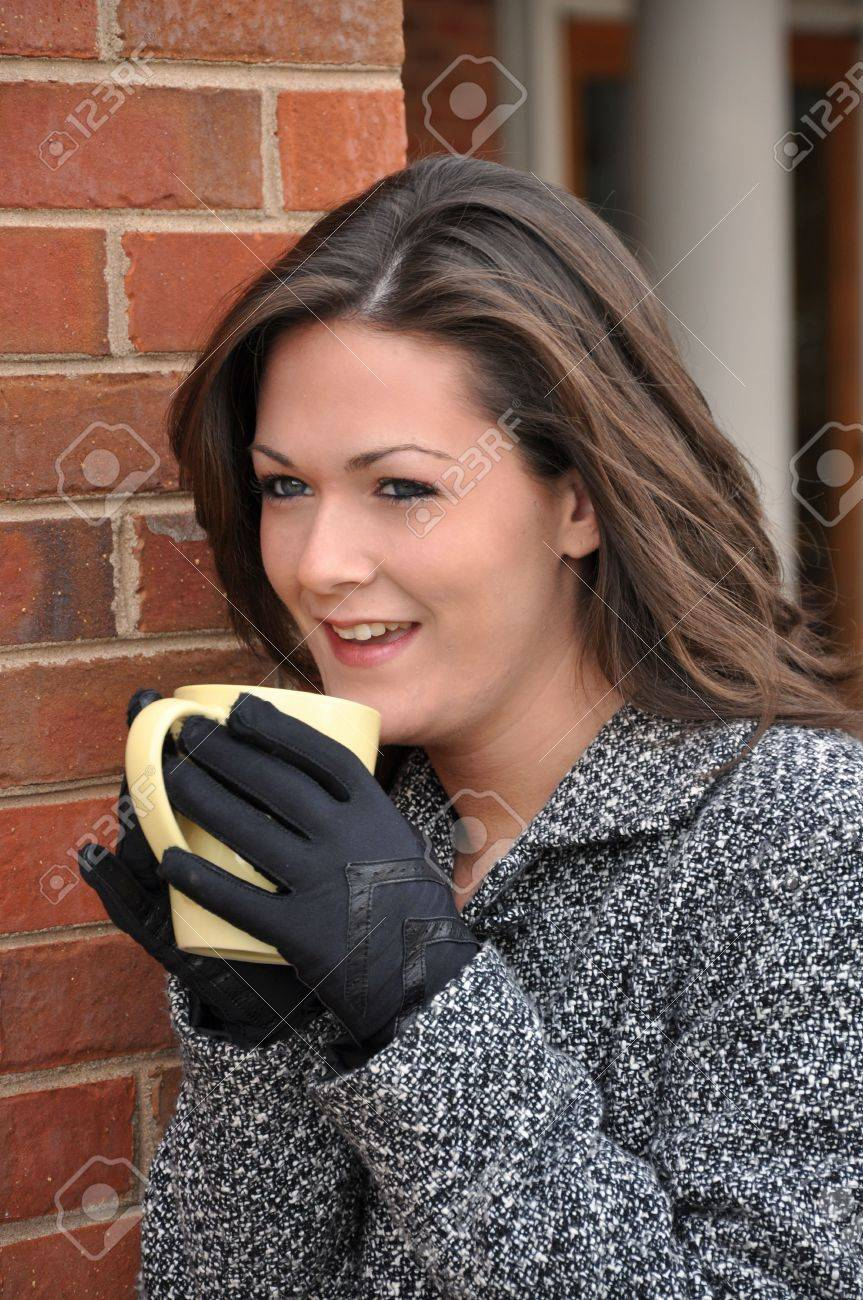 Girl drinking coffee outside with coat on. Stock Photo - 4033260