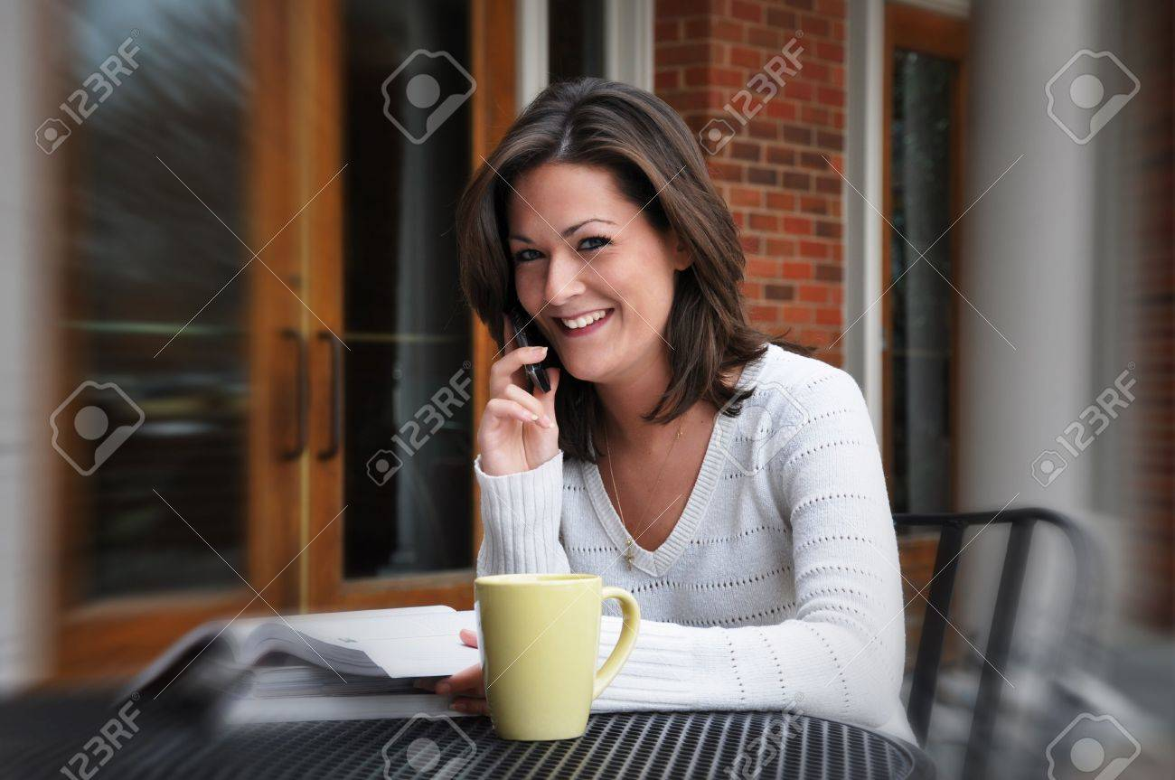 Female student studying while talking on cell phone.  Coffee in foreground. Stock Photo - 4055308