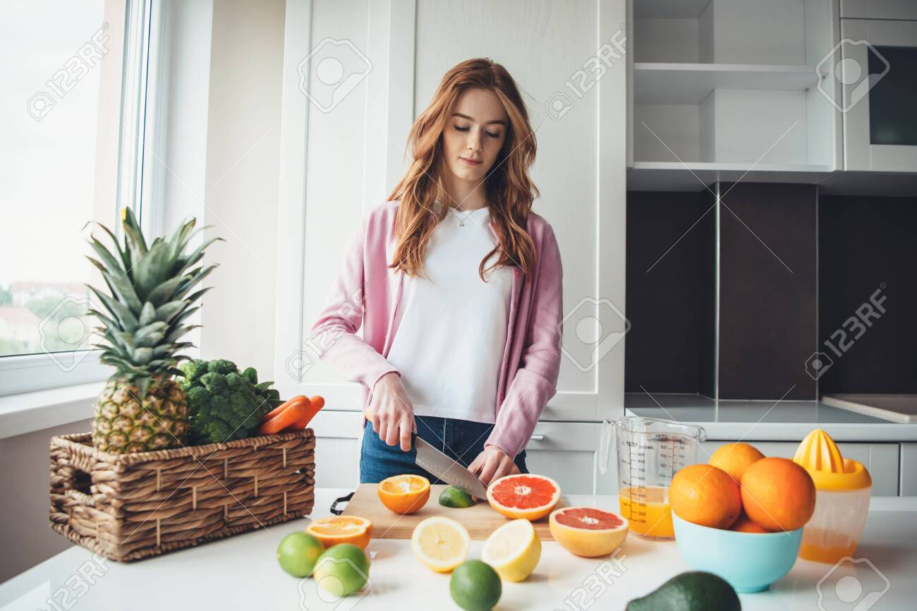 Ginger lady with freckles slicing fruits before squeezing the for juice - 148681815