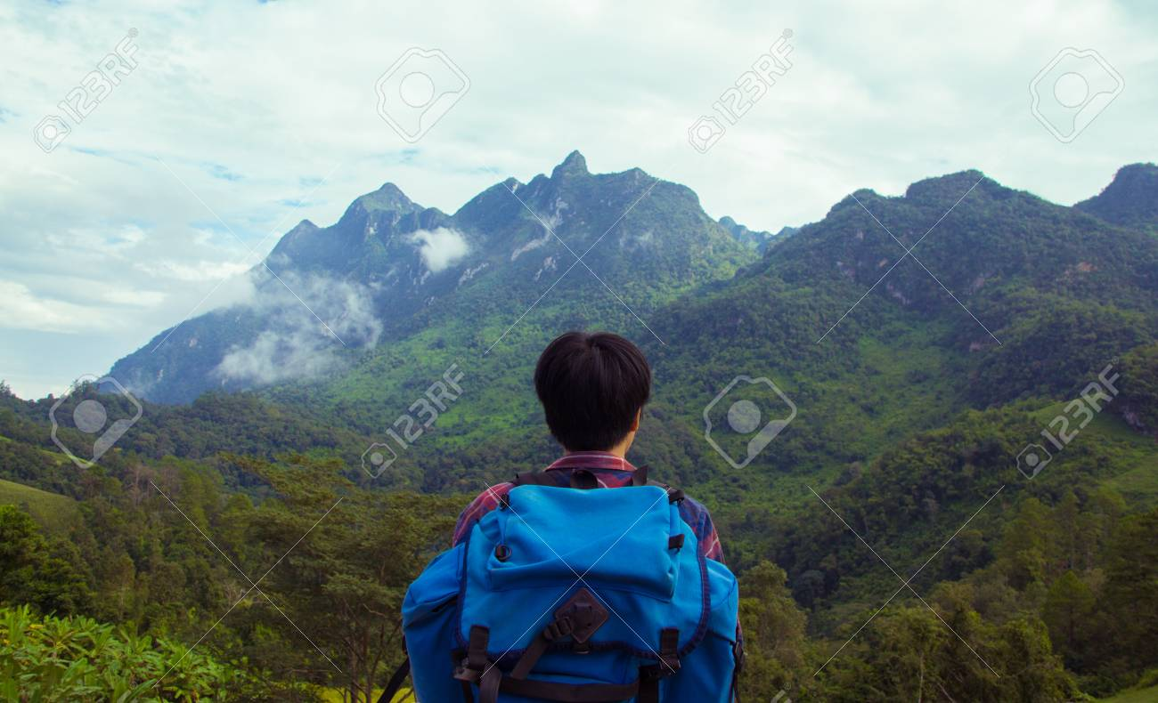 1cdd5aad39a Asian young man in Scottish shirt and black hat hiking at mountain..