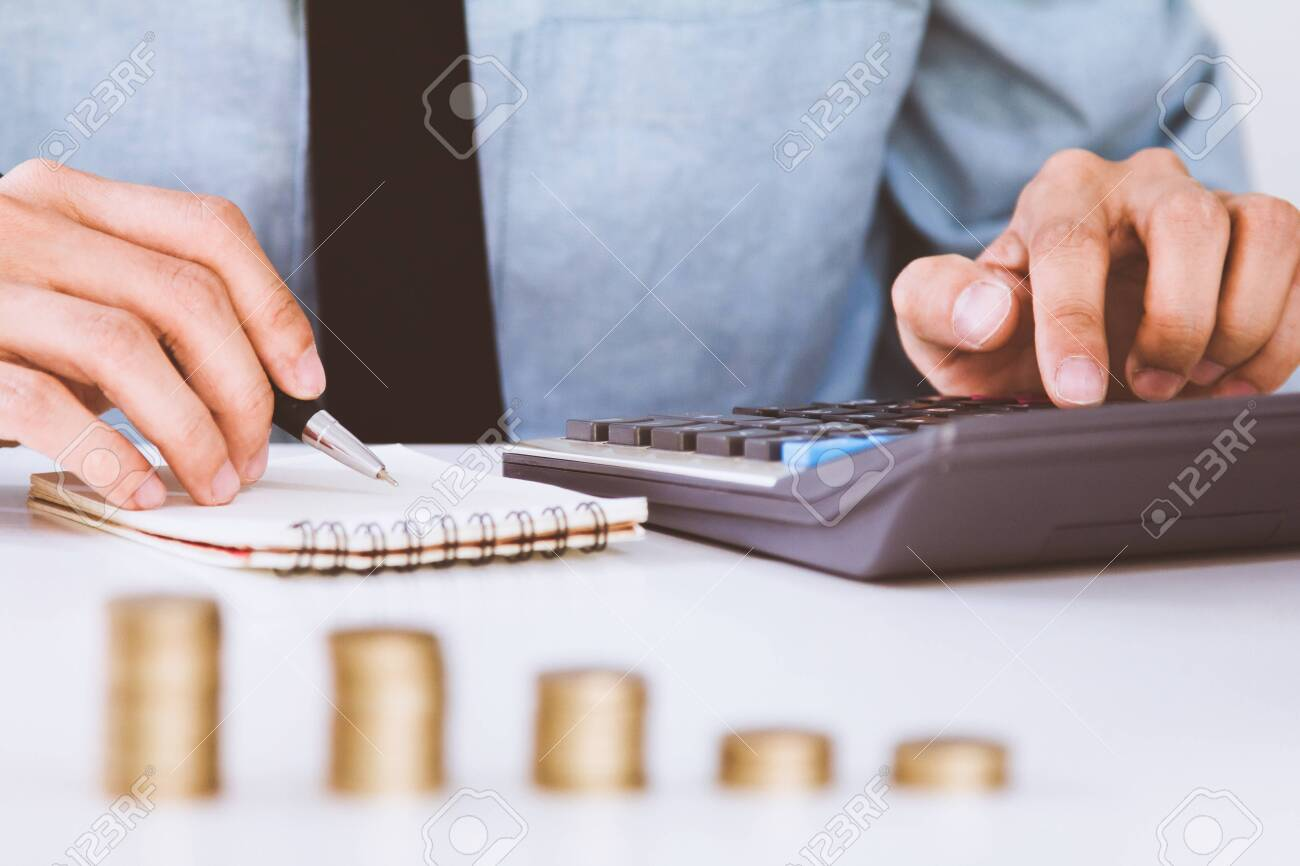 businessman hand using calculator Calculating bonus(Or other compensation) to employees to increase productivity.Writing paper on desk. - 121280670