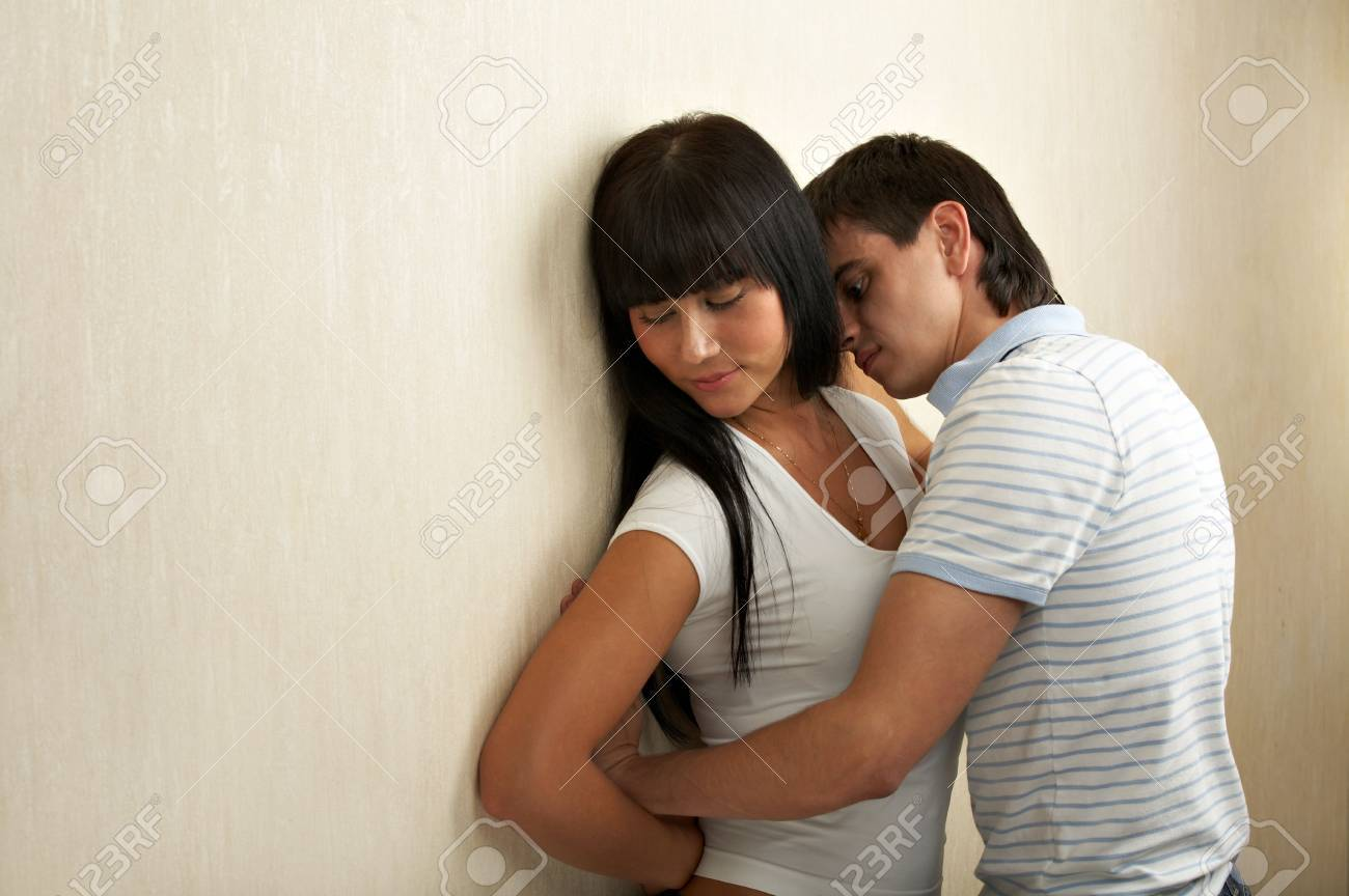 The guy embraces the beautiful girl at a wall Stock Photo - 3413504