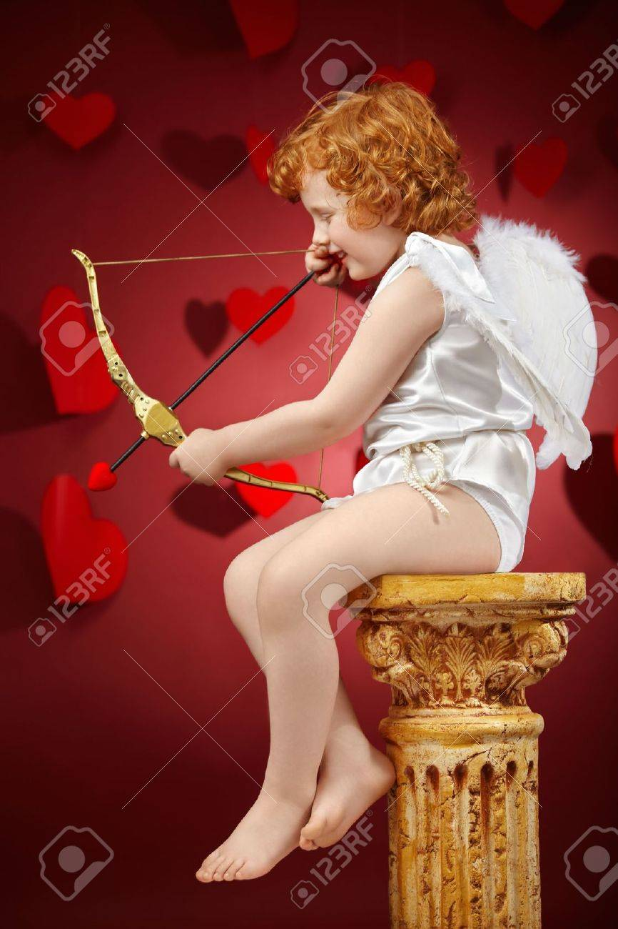 Profile of the small aiming boy - the cupid on a red background Stock Photo - 6328010