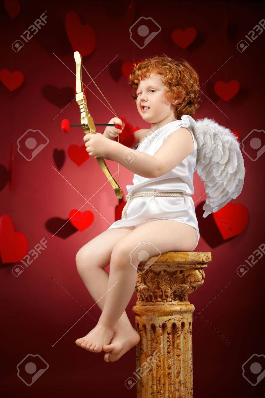 Small aiming boy in an image of the cupid on a red background Stock Photo - 6328134