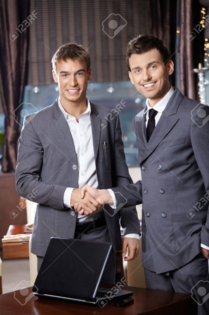 Two smiling business men shake hands each other at a meeting at restaurant Stock Photo - 6328524