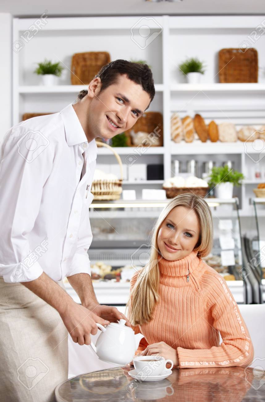 The young waiter pours tea to the attractive girl Stock Photo - 7841596
