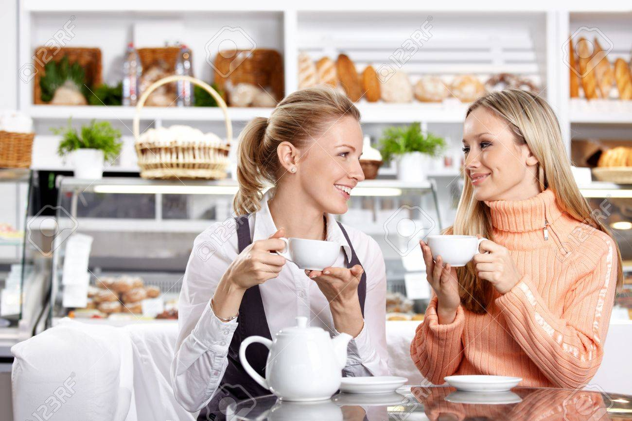 Two nice girls drink tea in cafe Stock Photo - 7841776