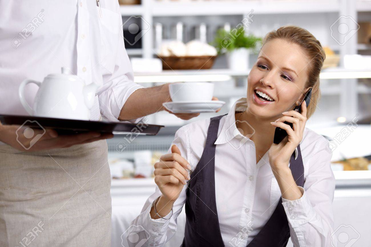 The girl speaking on the phone waits a coffee cup in cafe Stock Photo - 7841311