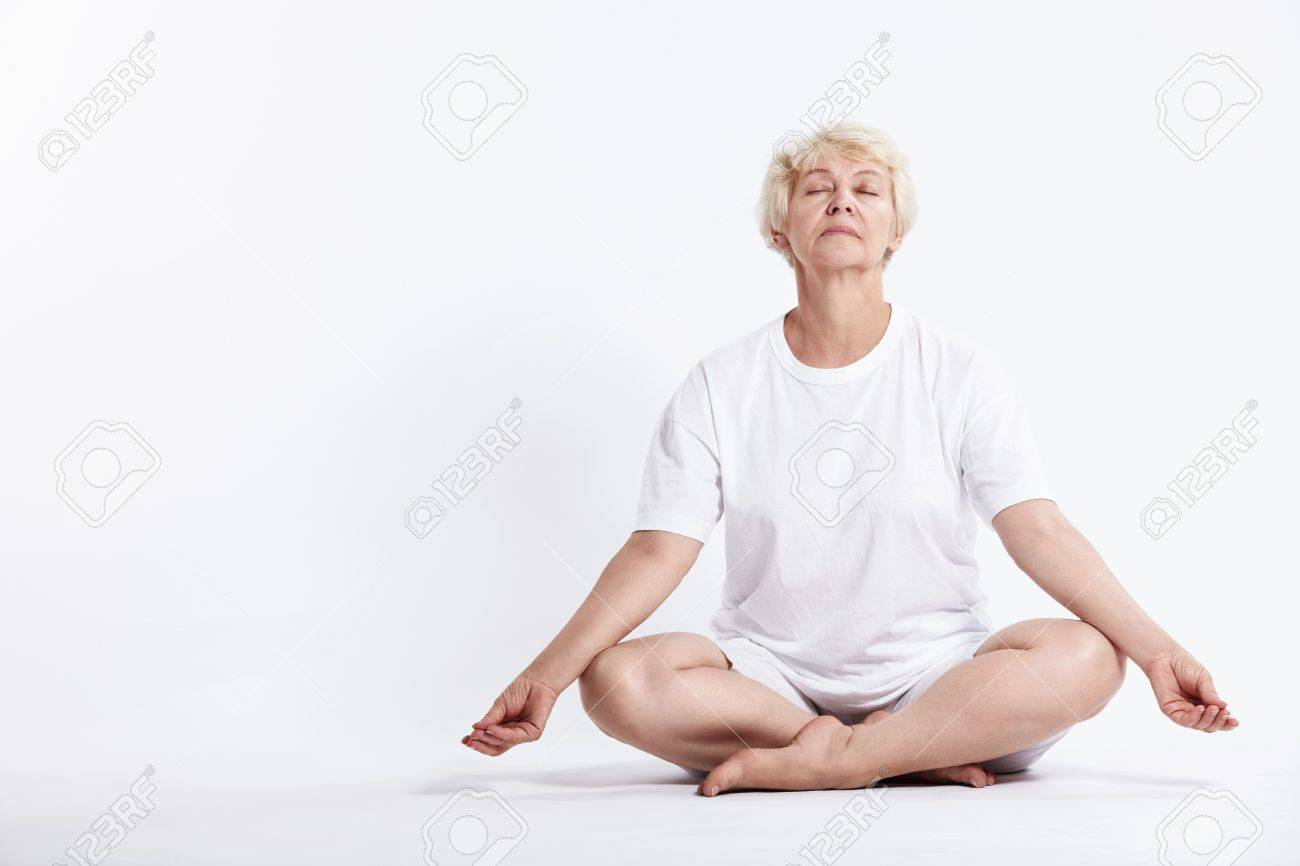 Mature woman in lotus position on a white background Stock Photo - 7945024