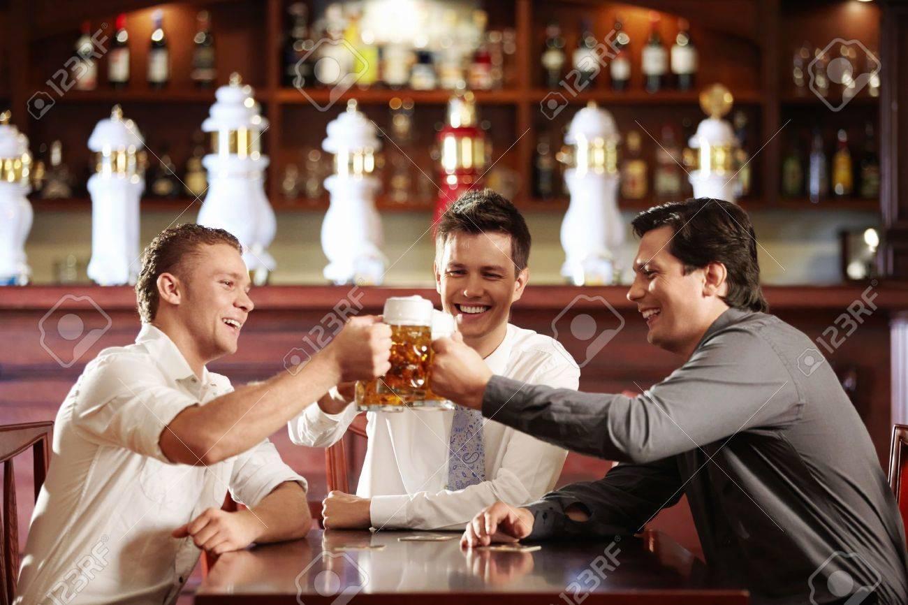 Three young men bob mugs in the bar Stock Photo - 8096779