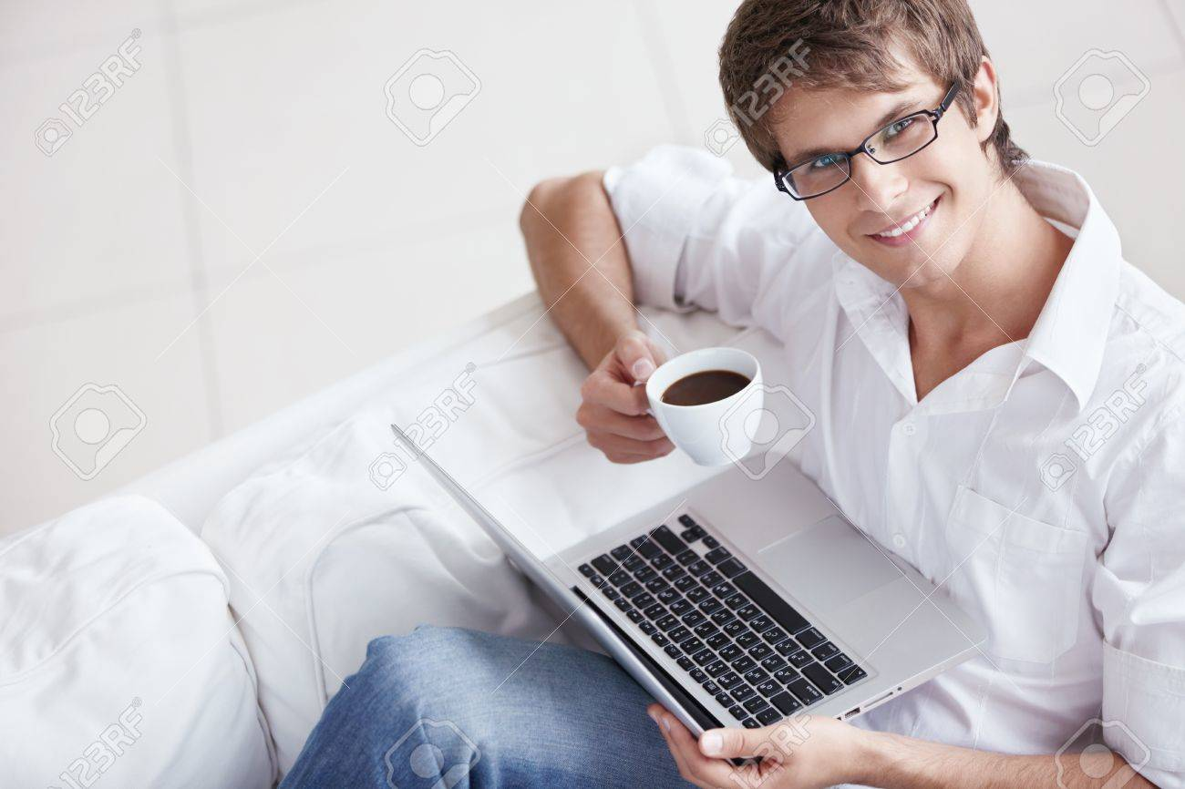 A young man with a cup and laptop Stock Photo - 8131601