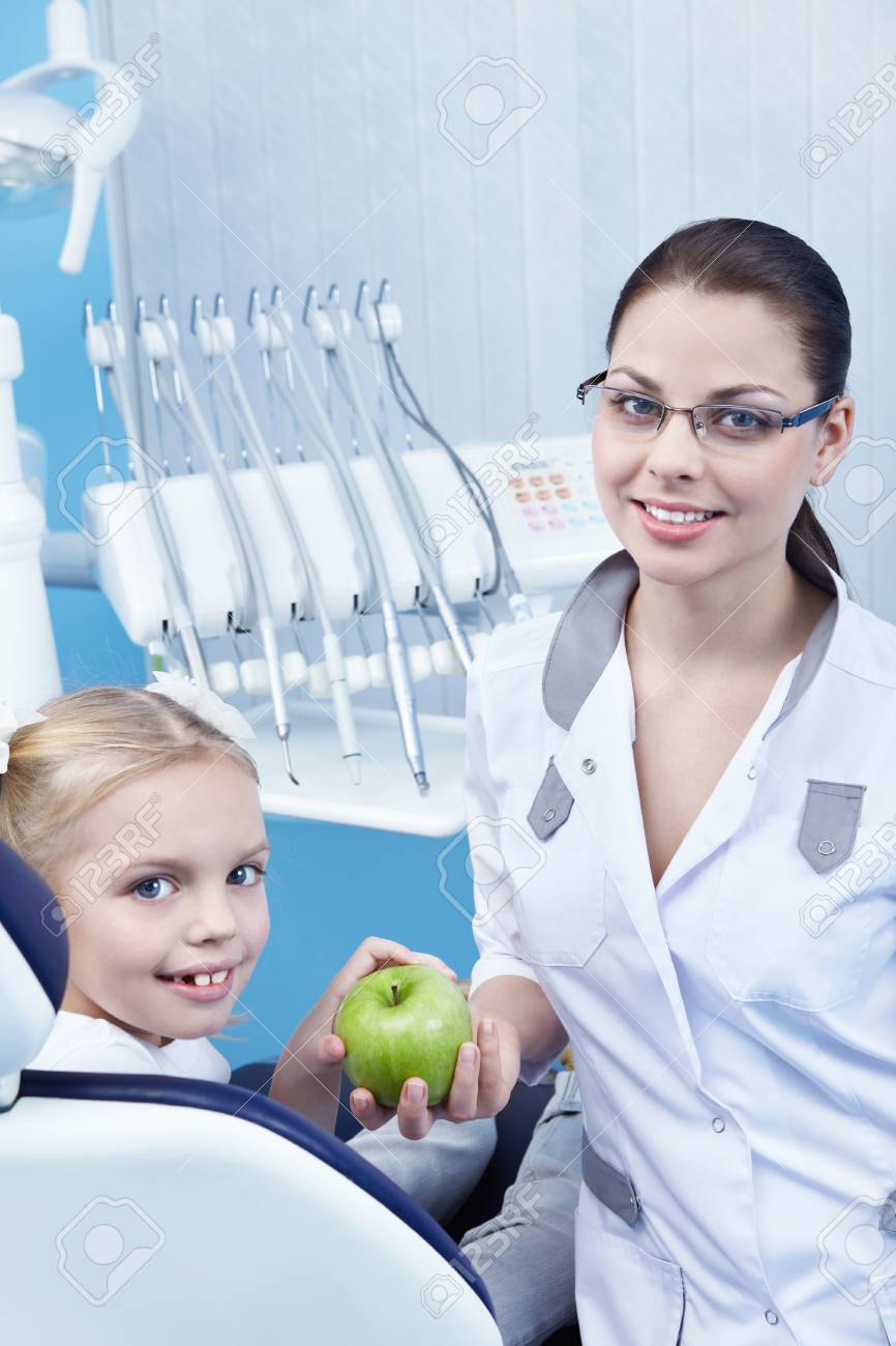 The doctor gives the child a green Apple Stock Photo - 8695704