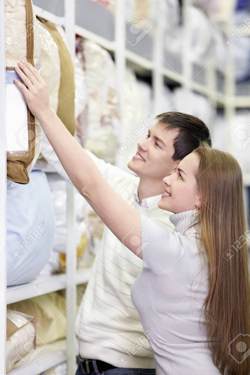 The happy couple chooses a pillow in the store Stock Photo - 8695470