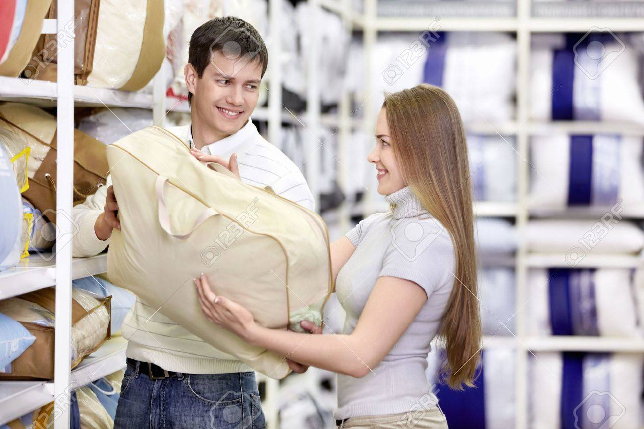 Man gives a girl the pillow in the store Stock Photo - 8800390