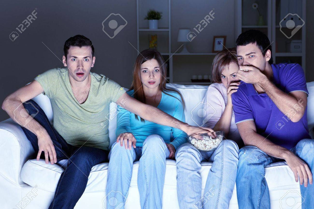 Young attractive people are watching TV at home Stock Photo - 8969978
