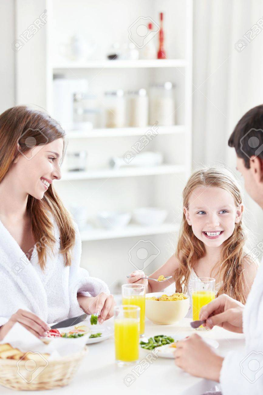 A happy family with a child eat breakfast in the kitchen - 10432036