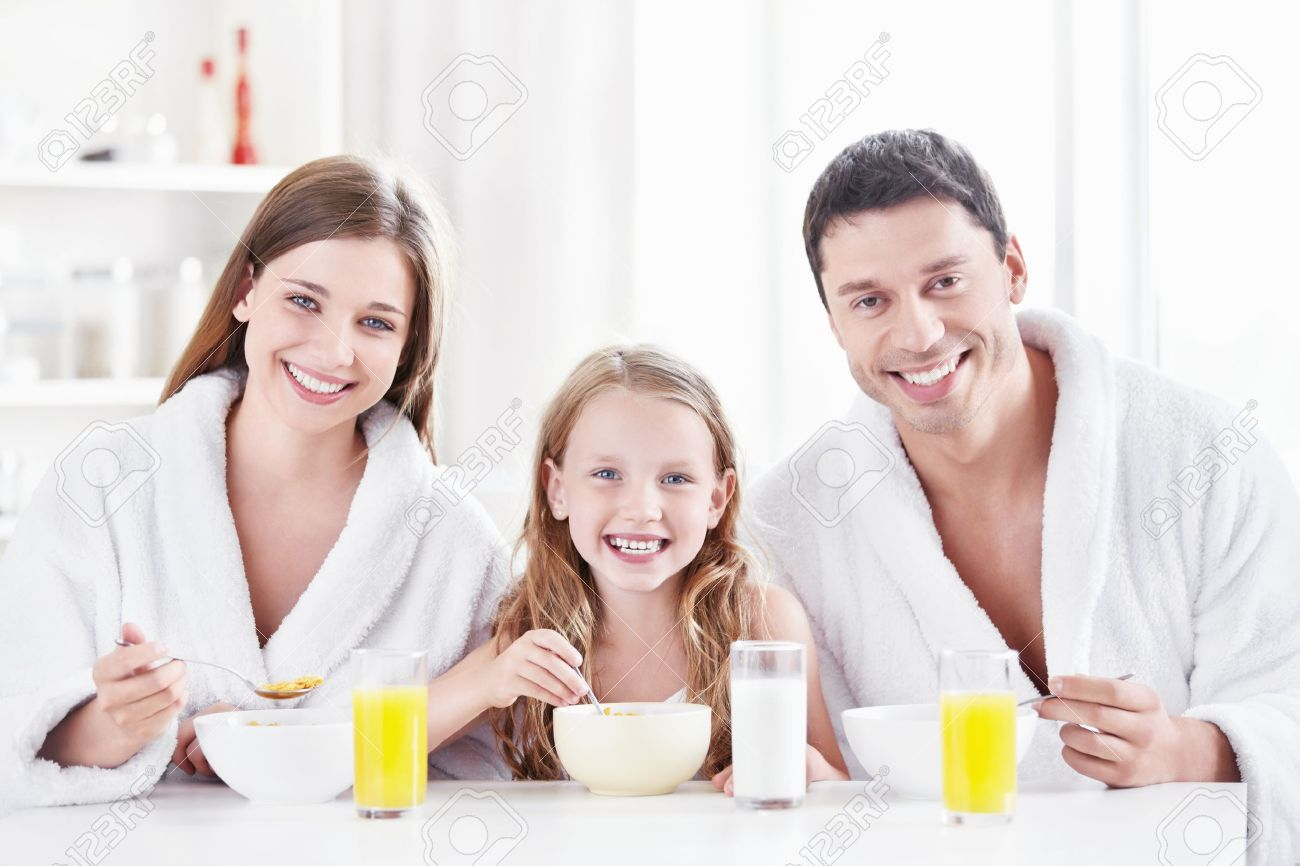 Happy family in kitchen - A Happy Family With A Child In The Morning In The Kitchen Stock Photo 10432032