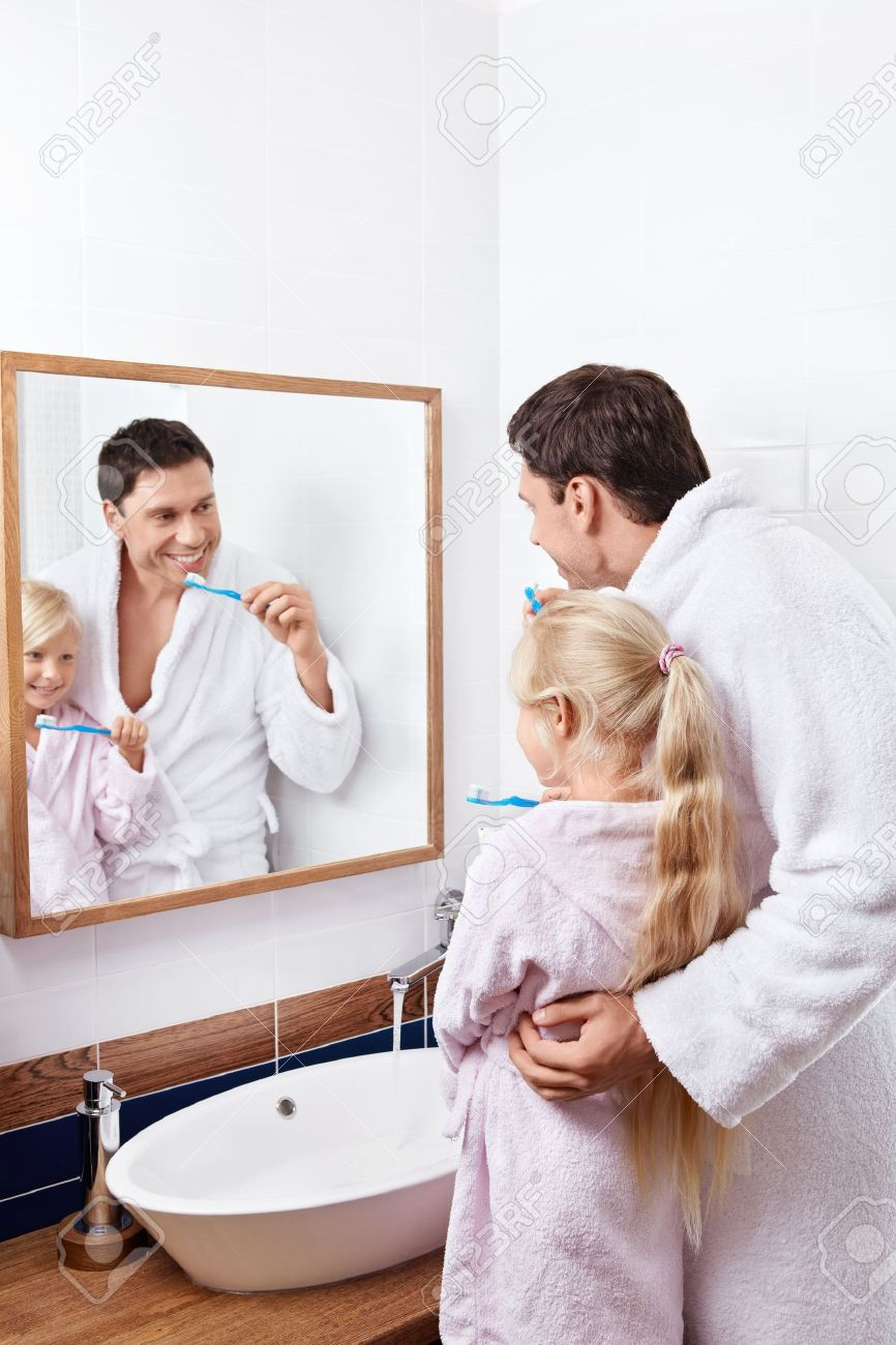 . Father and daughter brushing their teeth in the bathroom