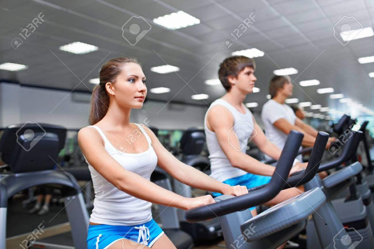 Young people on treadmills at fitness club Stock Photo - 14447032