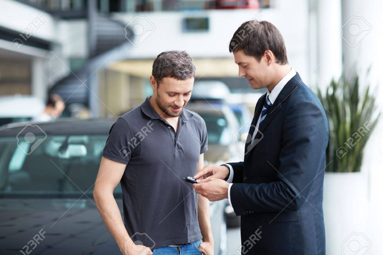 Young man with a salesman in a motor show Stock Photo - 15501845