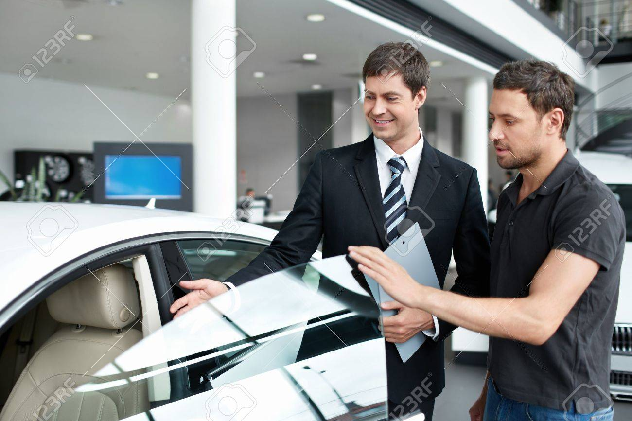 Young man with a salesman in a motor show Stock Photo - 15501841