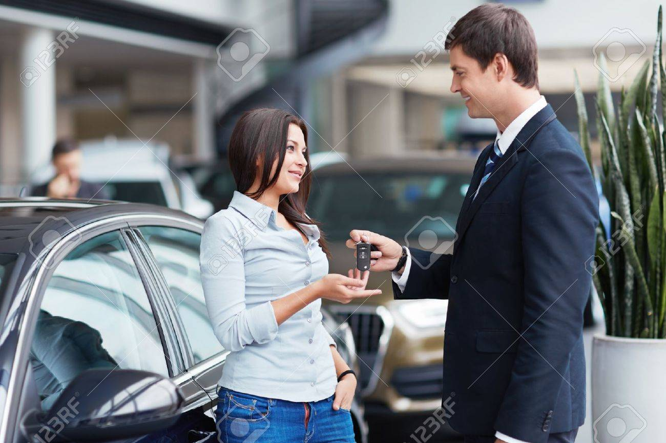 Seller gives keys to car girl in the salon Stock Photo - 15573185