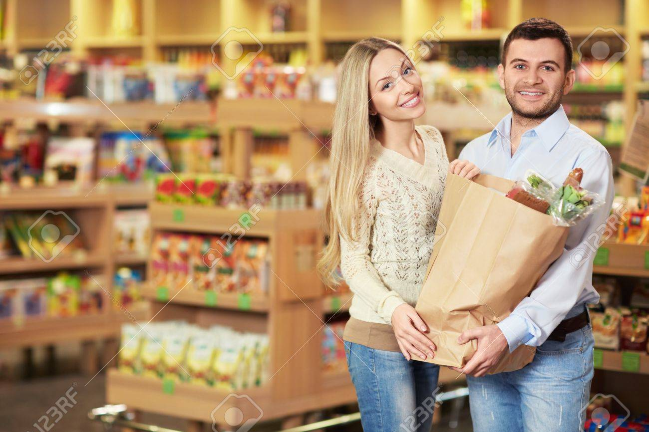 Young couple with package of products in store Stock Photo - 18357768
