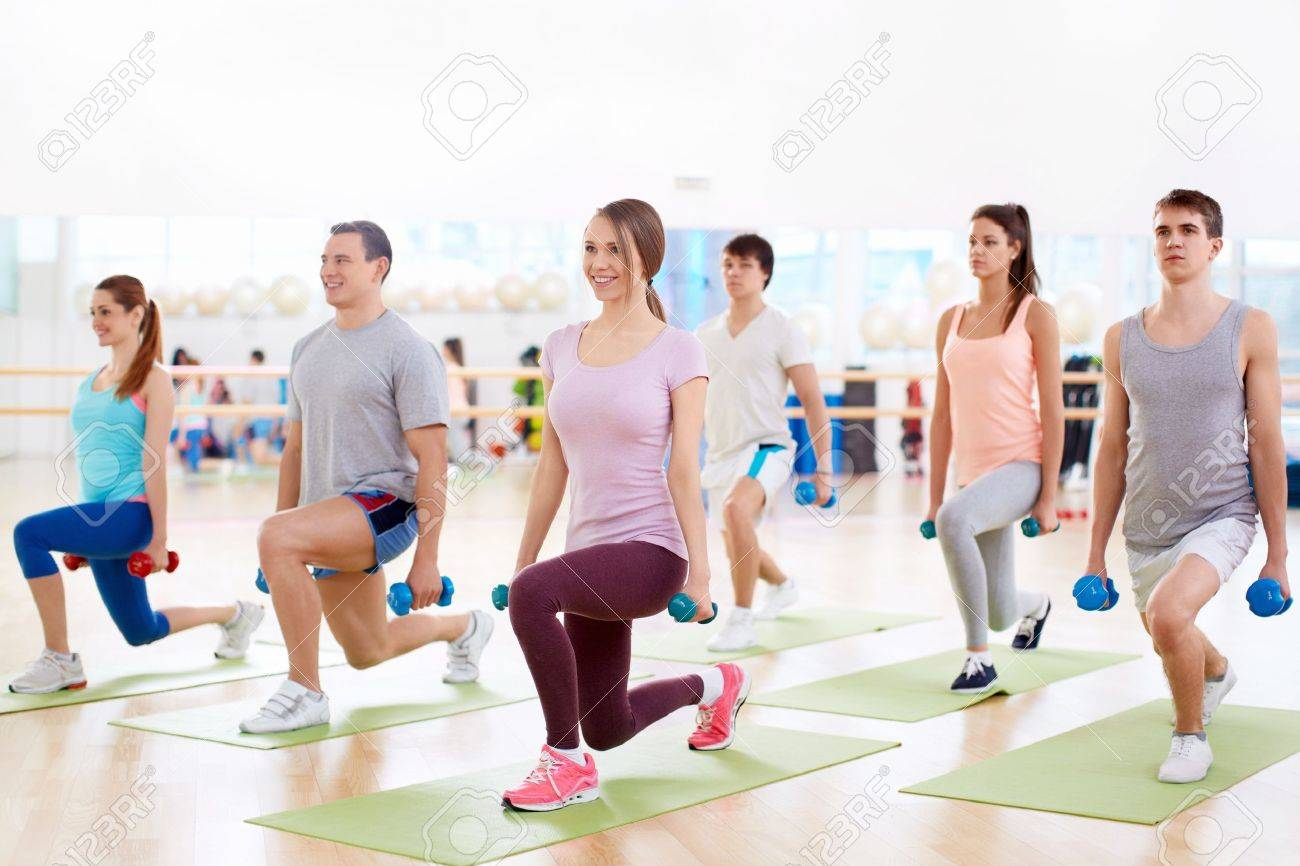 Young people with a dumbbell in fitness club Stock Photo - 18941020