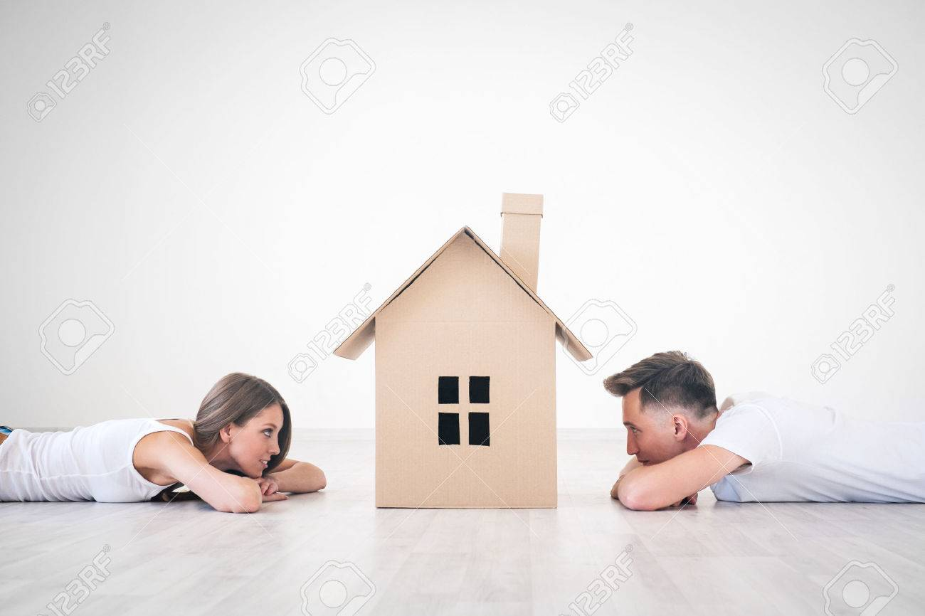 Daydreaming Young Couple At Home Stock Photo