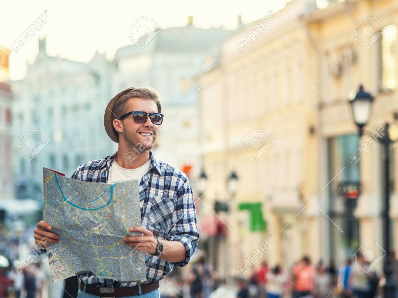 Young man with a map outdoors - 38046373