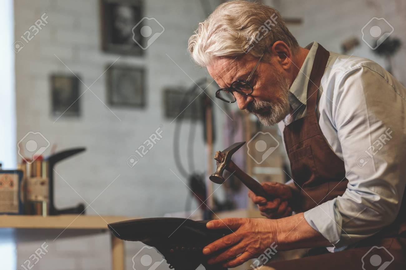 An elderly shoemaker in uniform at work - 104482780