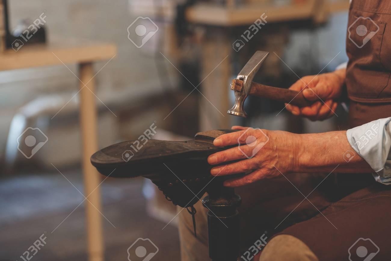 An elderly shoemaker at work - 104482790